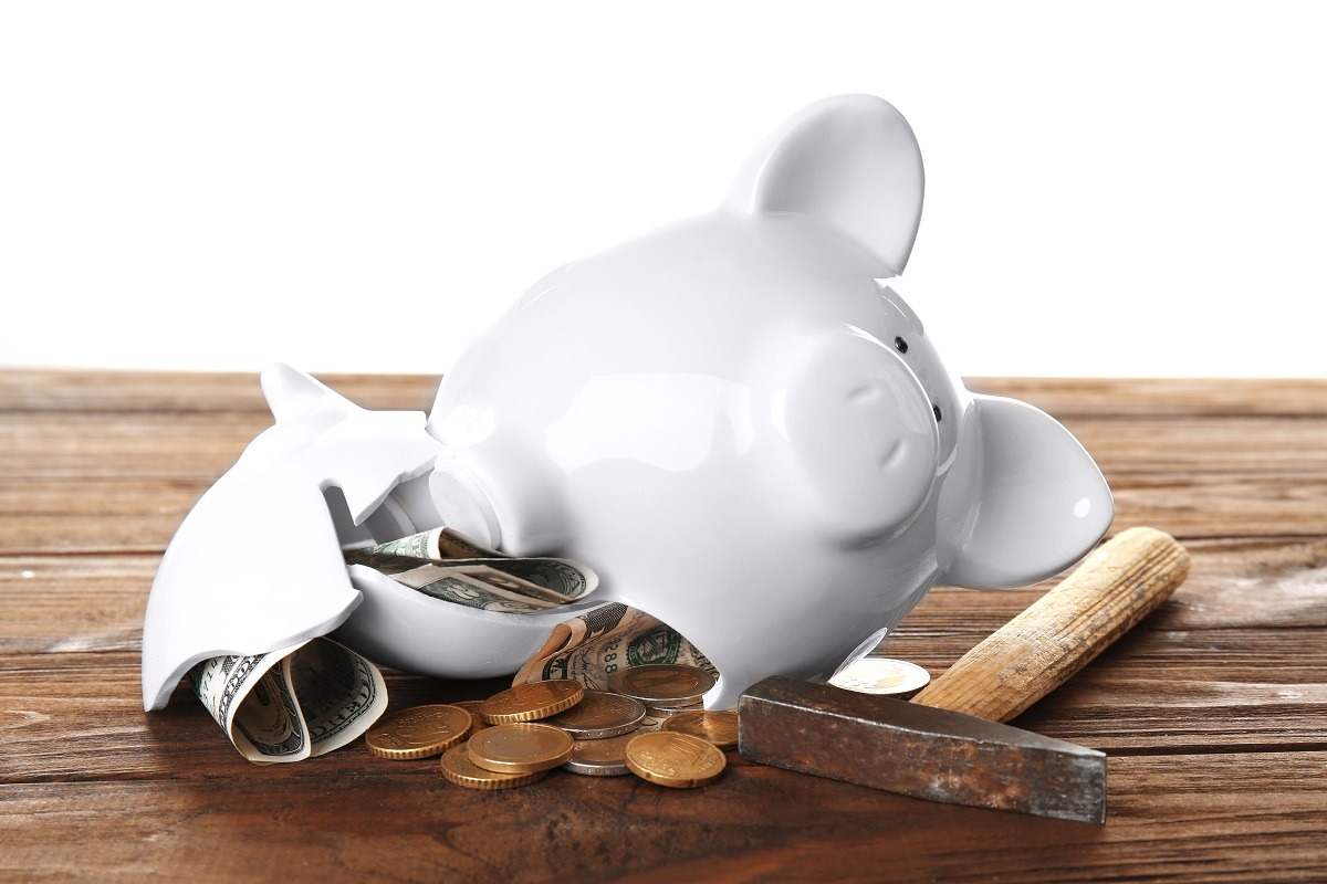 Broken piggy bank with money and hammer on white background