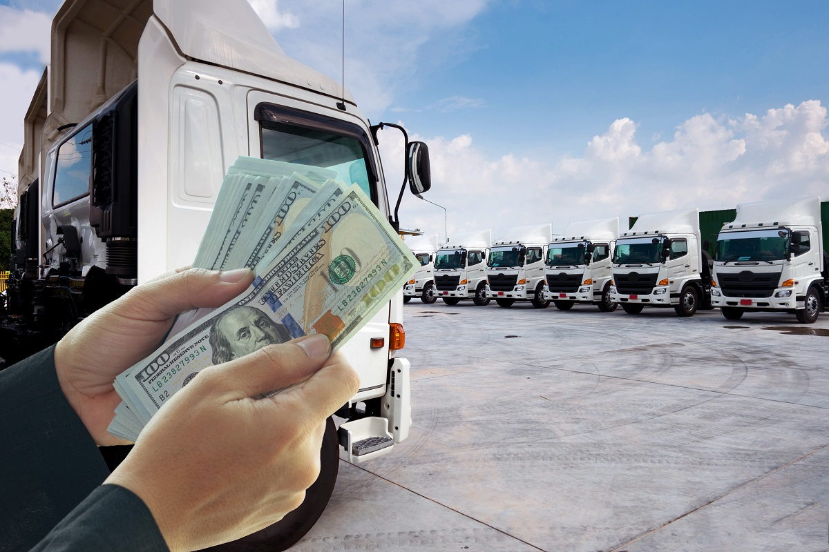 People hands are taking money to buy new truck fleet as in business logistics concept.