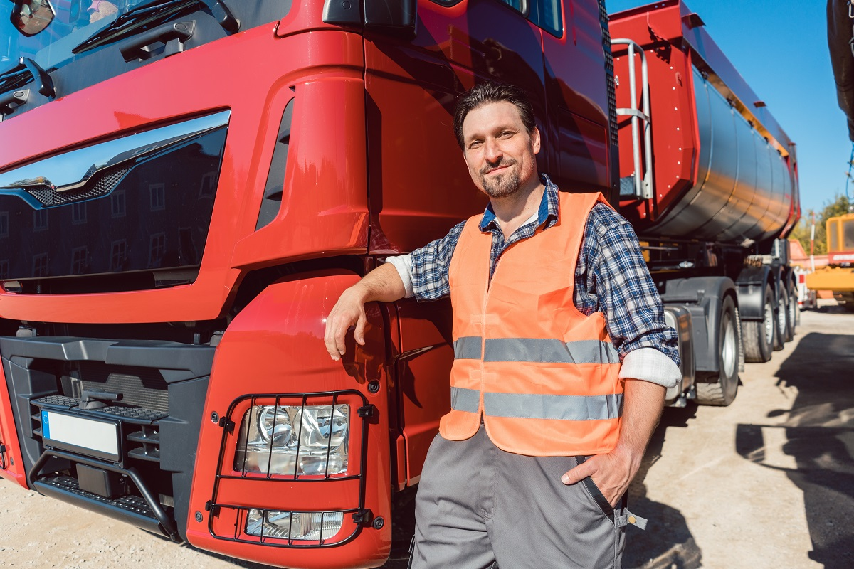 Truck driver in front of his freight forward lorry