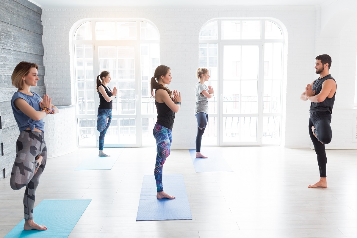 Yoga men instructor teaches group of people, fitness, sport and healthy lifestyle concept. Young women with personal trainer doing yoga exercises on mat in gym studio