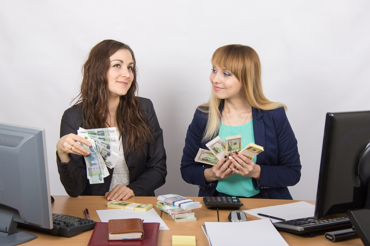 Two happy office girls are discussing a lot of money, which is held in the hands of