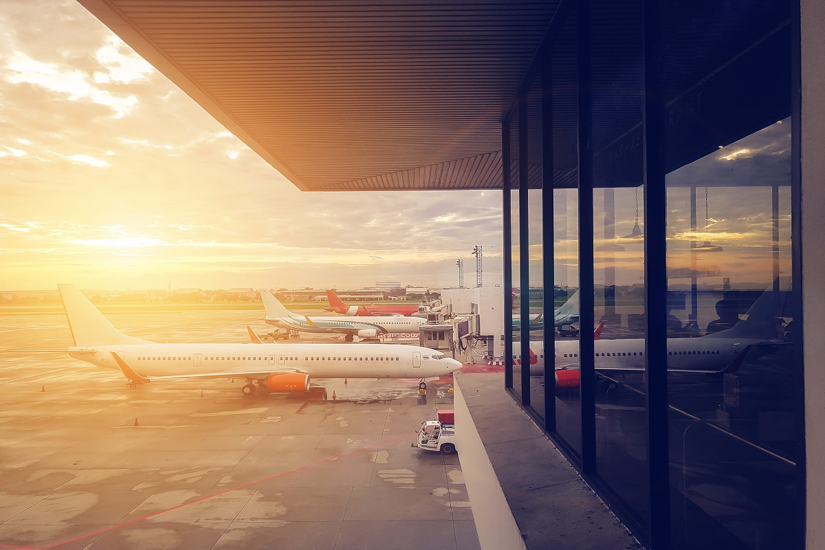 airplane at the airport terminal gate, modern international airport during sunset. transportation by plane and travel concept
