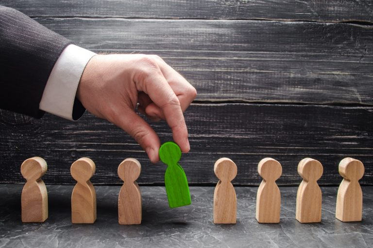 hand of a businessman takes a wooden figure of a man. The concept of search, hiring and firing workers, promotion. Business tactics and strategy, management, business management.