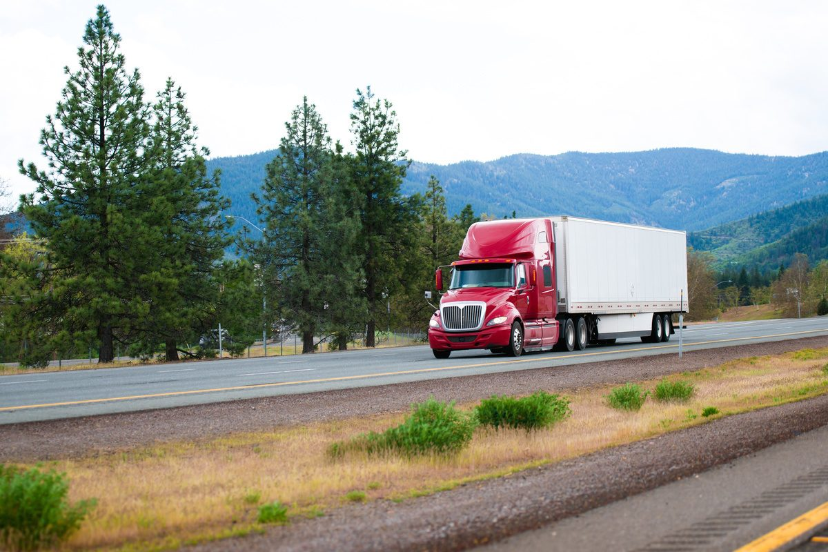 Red modern semi truck with dry van trailer moving by divided highway I-5 in California